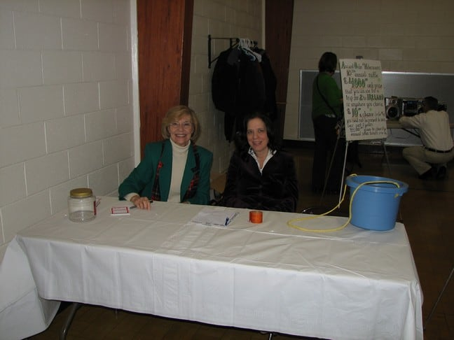 Mary Ellen McFadden and Kim Perry guarding the entrance and peddling 50/50 tickets